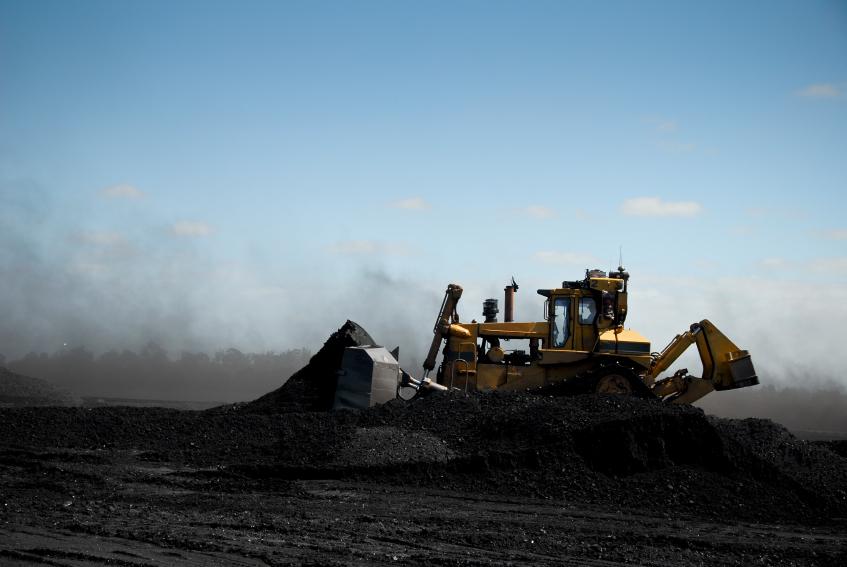 A heavy bulldozer pushing coal.