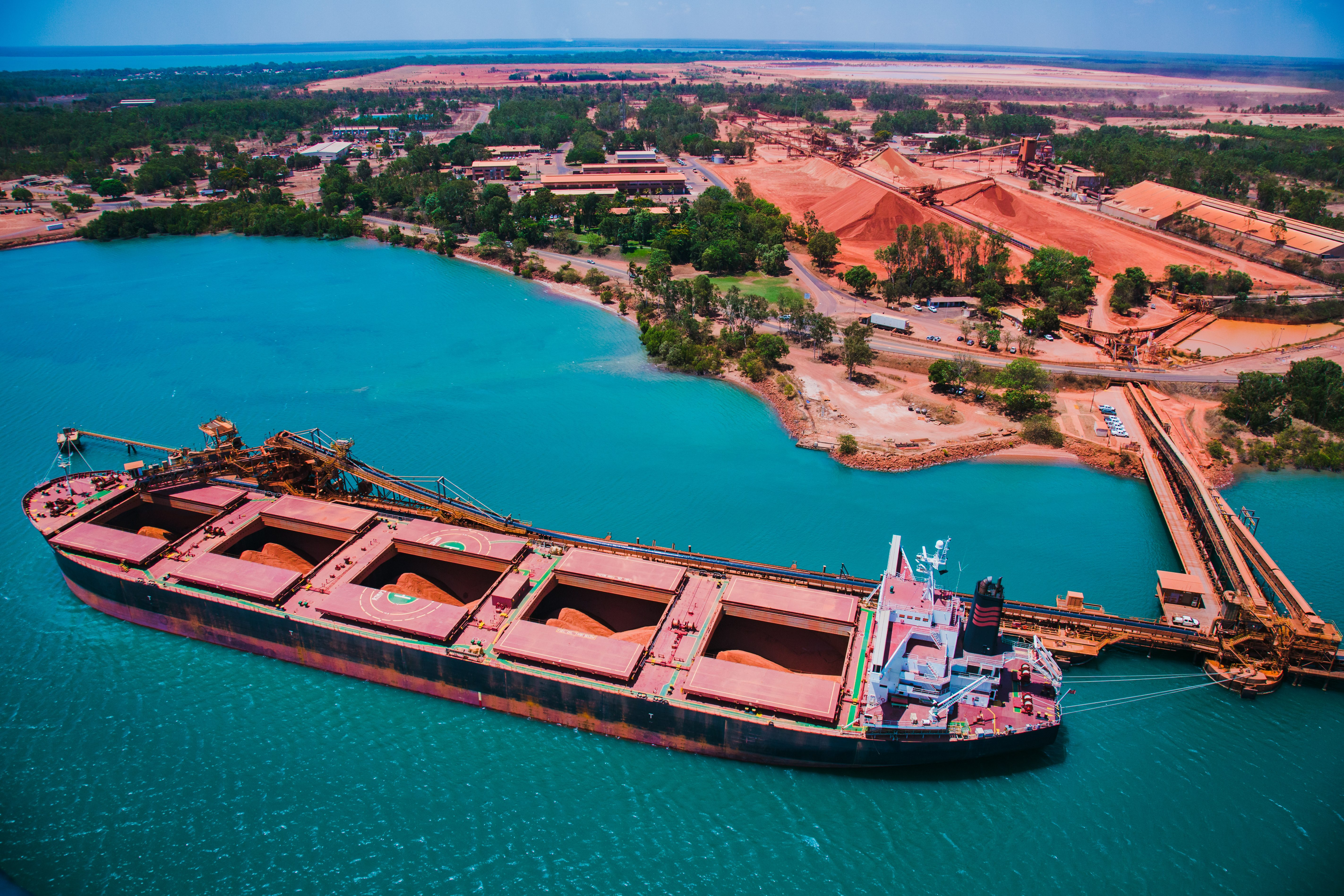 S. Ship being loaded at Rio Tinto Weipa operations with bauxite stockpiles in the background