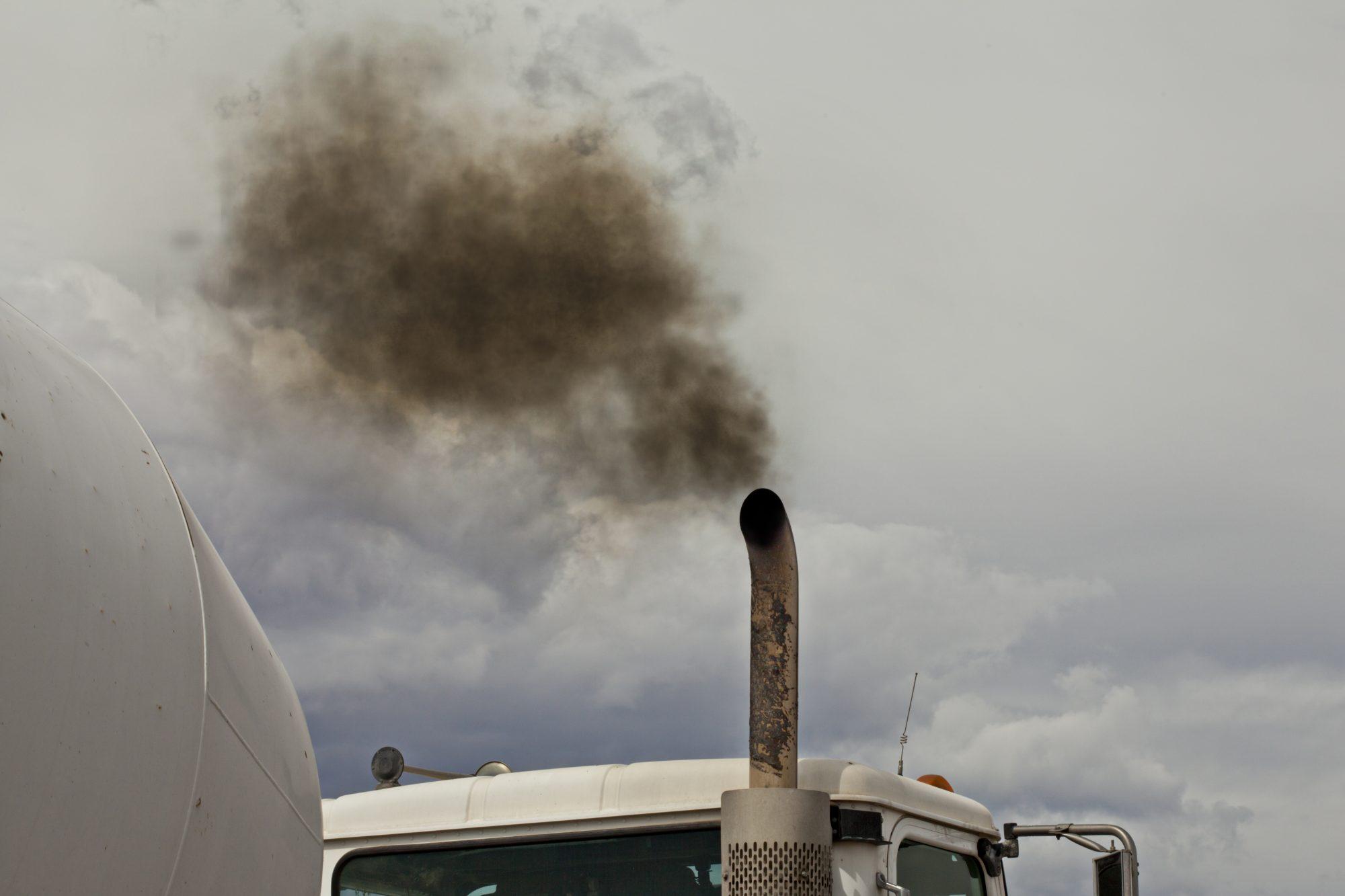 A white dump truck spews black exhaust smoke into a blue sky.